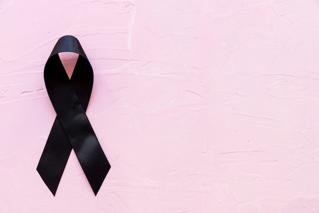 Trauer- und melanomschwarzband auf rosa hintergrund
