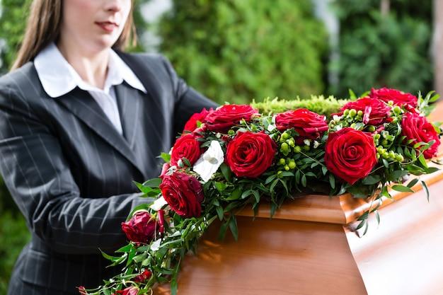 Trauerfrau am begräbnis mit sarg