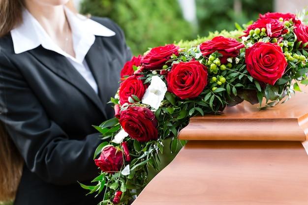 Trauernde frau bei der beerdigung mit sarg
