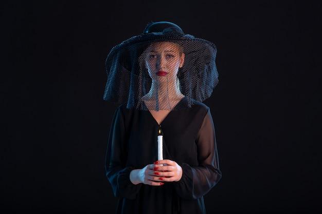 Trauernde frau in schwarz gekleidet mit brennender kerze auf schwarzem schreibtisch tod traurigkeit beerdigung