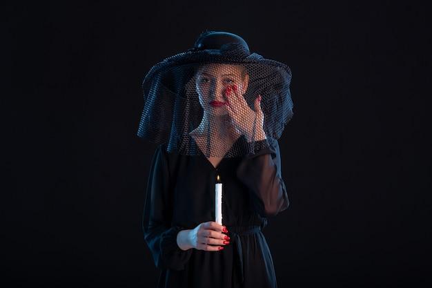 Trauernde frau in schwarz gekleidet mit brennender kerze auf schwarzer oberfläche tod traurigkeit beerdigung