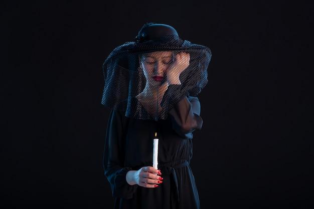 Trauernde frau in schwarz gekleidet mit brennender kerze auf schwarzer oberfläche traurigkeit begräbnistod