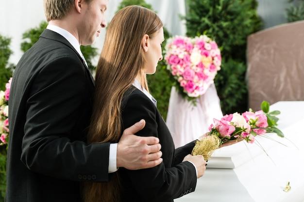 Trauernde menschen bei der beerdigung mit sarg