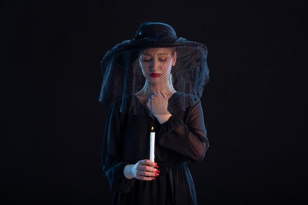 Trauernde, schwarz gekleidete frau mit brennender kerze auf einem schwarzen trauerbegräbnistod