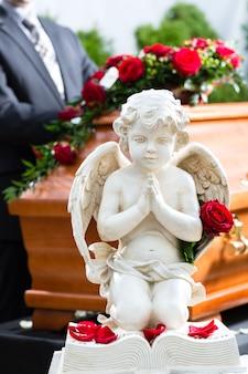 Trauernder mann bei der beerdigung mit sarg