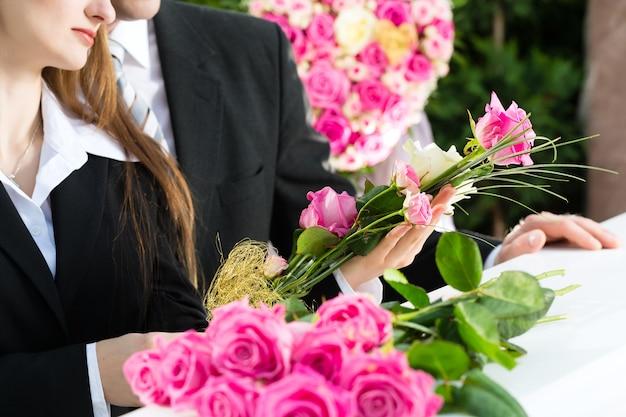 Trauernder mann und frau auf beerdigung mit rosa rose, die am sarg oder am sarg steht
