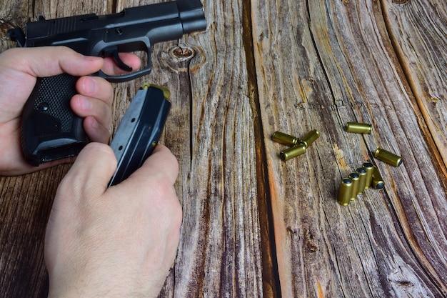 Traumatische patronen sind auf einem braunen holzhintergrund verstreut. hände halten einen pistolenclip und eine pistole