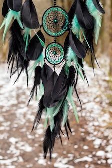 Traumfänger mit federn fäden und perlen seil hängend. traumfänger handgefertigt
