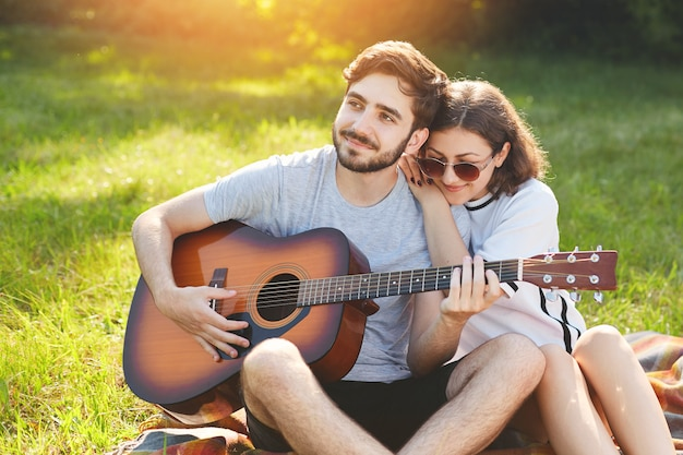 Traumhafte romantische paare sitzen auf grünem gras, genießen zusammengehörigkeit. der hübsche bärtige mann spielt gitarre und ihre freundin lehnt sich an seine schulter und hört serenaden. menschen- und beziehungskonzept