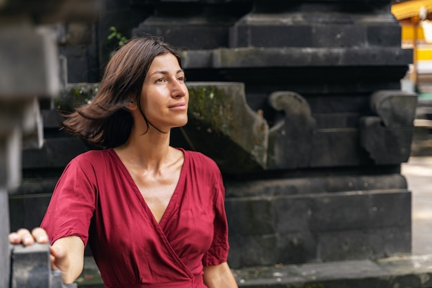 Traumhafte stimmung. erfreutes brünettes mädchen, das ein lächeln auf ihrem gesicht behält, während sie an ihre reise denkt