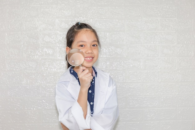 Traumkarrierekonzept, porträt des glücklichen kindes im wissenschaftsmantel mit lupe auf unscharfem hintergrund