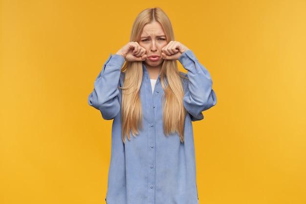 Traurig aussehende frau, weinendes mädchen mit langen blonden haaren. blaues hemd tragen. menschen- und emotionskonzept. schmollen sie über ihre lippen und wischen sie sich die tränen ab. beobachten in der kamera, isoliert über orange hintergrund