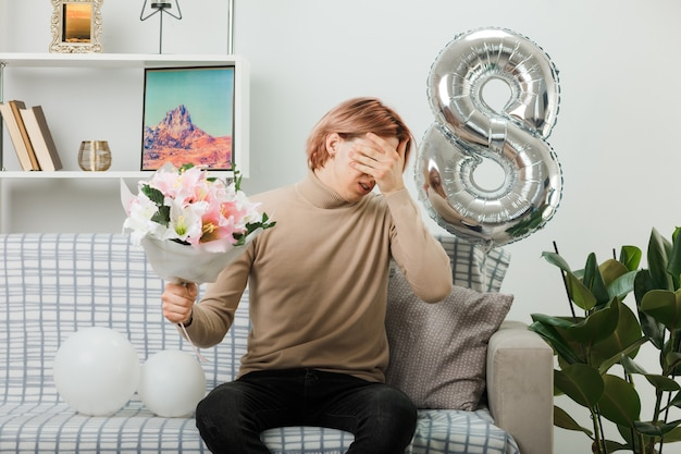 Traurig bedecktes gesicht mit einem gutaussehenden kerl am glücklichen frauentag, der einen blumenstrauß auf dem sofa im wohnzimmer hält