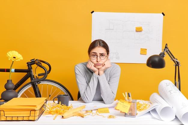 Traurig gelangweilte professionelle architektin macht bauskizzen und erstellt projekt lehnt sich die hände unter kinnposen im coworking space an, fühlt sich während des arbeitstages im büro müde. arbeitsablauf in der werkstatt