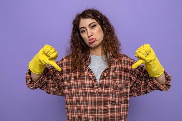 Traurig mit daumen nach unten junge putzfrau mit handschuhen isoliert auf lila wand