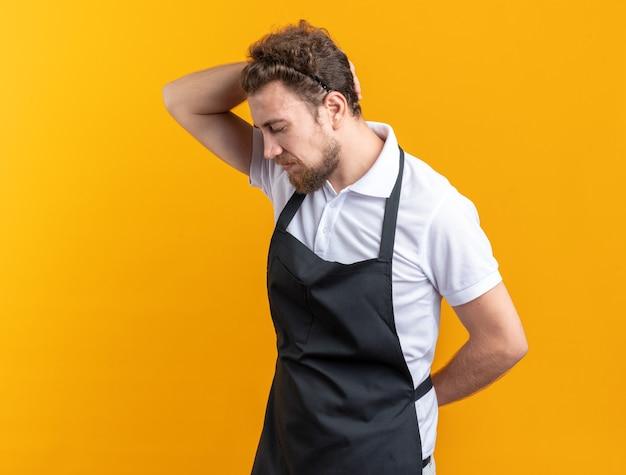 Traurig mit geschlossenen augen junger männlicher friseur in uniform, der die hand auf den hals legt, isoliert auf gelbem hintergrund