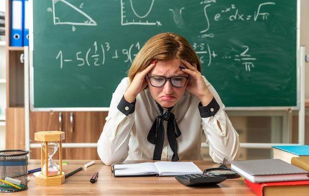 Traurig mit gesenktem kopf junge lehrerin mit brille sitzt am tisch mit schulwerkzeugen, die im klassenzimmer die hände auf den kopf legen