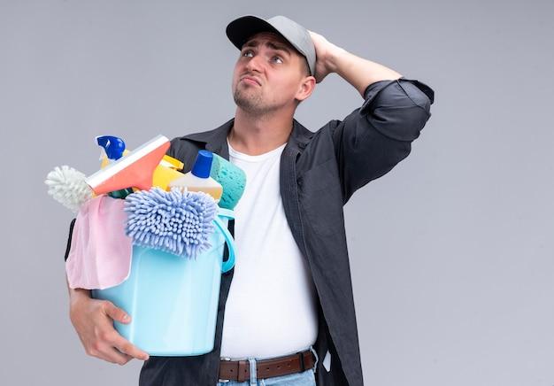 Traurig suchender junger hübscher reinigungsmann, der t-shirt und kappe hält, die eimer mit reinigungswerkzeugen hält, die hand auf kopf lokalisiert auf weißer wand setzen