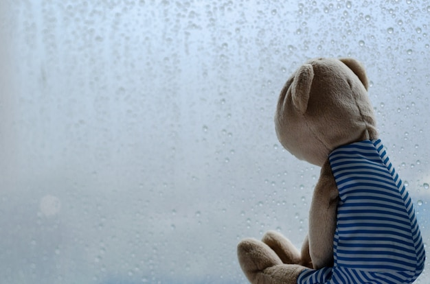 Traurig teddy bear, der heraus dem fenster am regnerischen tag sitzt und betrachtet.
