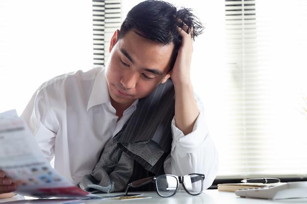 Traurig verwirrt und betont vom jungen asiatischen mann, der rechnungsschreiben der kreditkarteschuld, des finanzgeldproblems und des steuerrechnungsmeldungskonzeptes hält