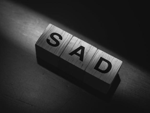 Traurig, wort auf holzwürfelblöcken auf dunklem hintergrund, schwarz-weiß-stil.