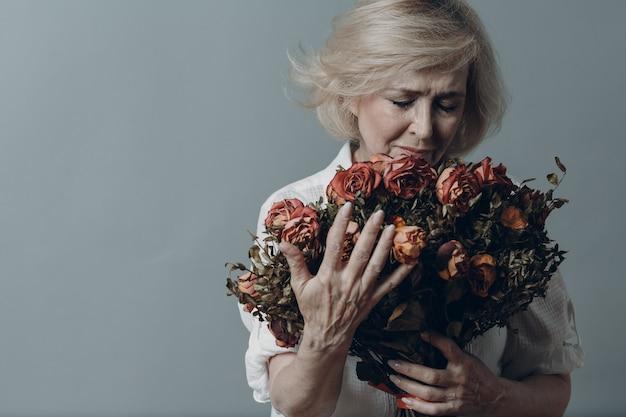 Traurige ältere frau berührt strauß verwelkter rosen