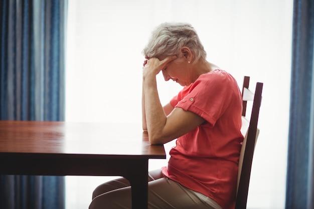 Traurige ältere frau, die an einem tisch sitzt