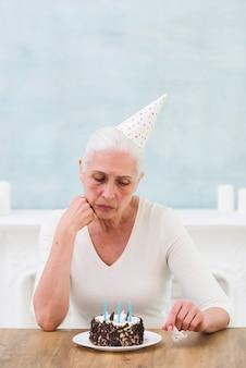 Traurige ältere frau, die geburtstagskuchen mit kerze über tabelle betrachtet