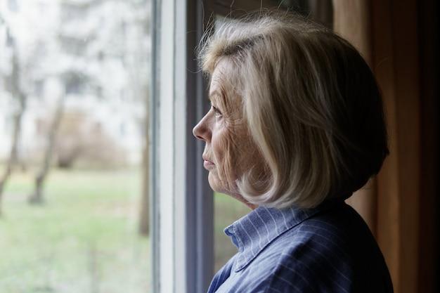 Traurige ältere frau, die heraus das fenster schaut