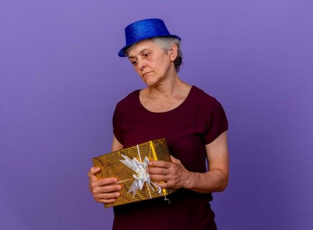 Traurige ältere frau, die partyhut trägt, hält geschenkbox, die unten auf lila wand mit kopienraum schaut