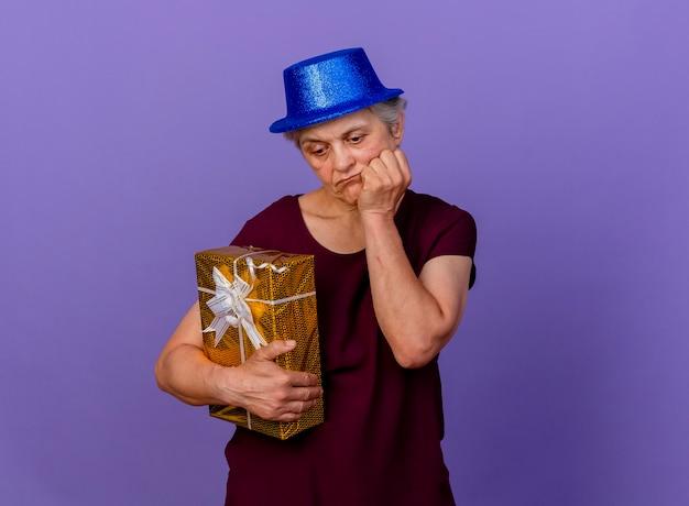 Traurige ältere frau, die partyhut trägt, legt hand auf kinn und hält geschenkbox lokalisiert auf lila wand mit kopienraum