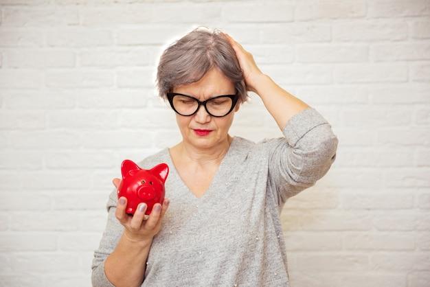 Traurige ältere frau mit rotem sparschwein auf weißem hintergrund. unhaltbarkeit von sozialtransfers und rentensystem