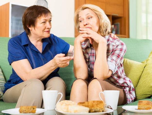 Traurige ältere frauen diskutieren probleme