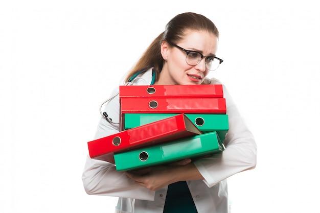 Traurige ärztin des attraktiven kaukasischen brunette, die im büro mit mappen in ihren händen steht