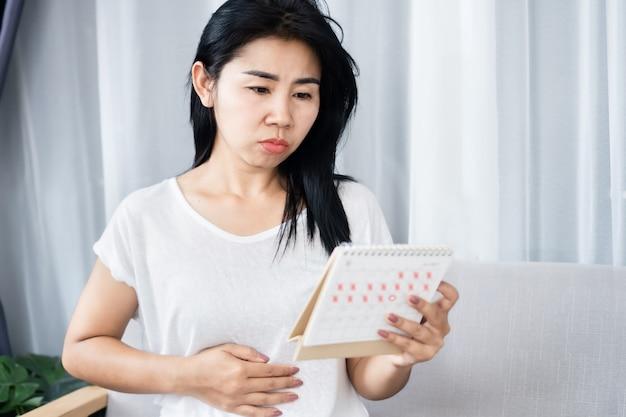 Traurige asiatische frau enttäuscht nicht schwangere hand mit kalender zu bekommen