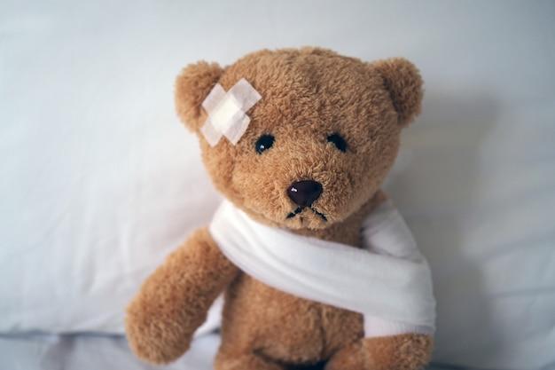 Traurige bärenpuppe, die krank im bett mit der wunde auf dem kopf und dem verband liegt