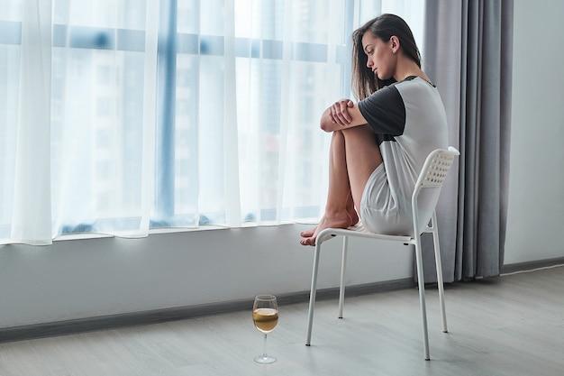 Traurige betonte unglückliche depressive melancholische nachdenkliche frau mit weinglas, die allein zu hause in der nähe des fensters während schwierigkeiten probleme leben und depression sitzt
