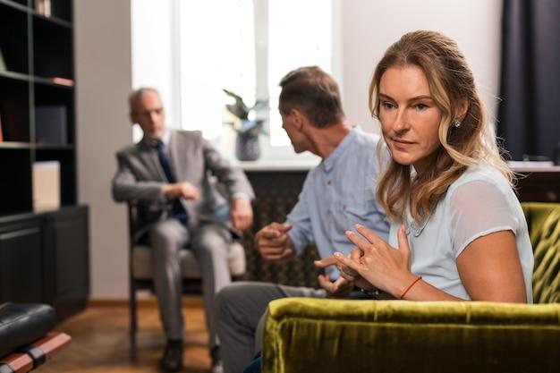 Traurige blonde frau mittleren alters, die neben ihrem mann im büro des psychoanalytikers auf dem sofa sitzt