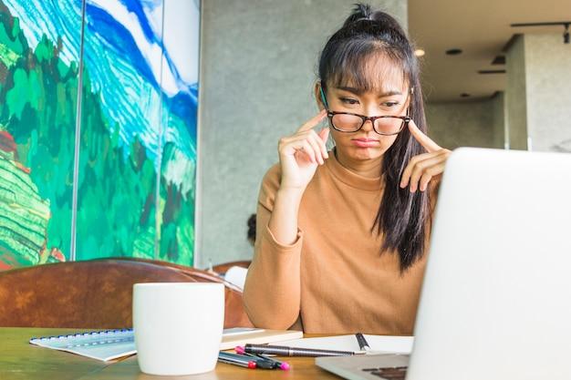 Traurige dame mit laptop bei tisch