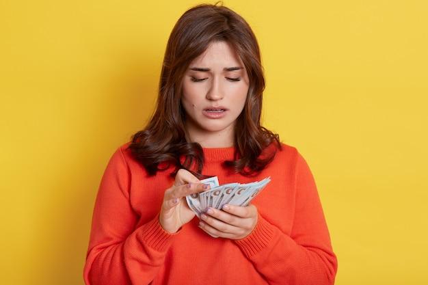 Traurige dunkelhaarige frau mit orangefarbenem pullover posiert isoliert über gelber wand, zählt ihr gehalt, hat nicht genug geld, ist verärgert und hält banknoten in händen.