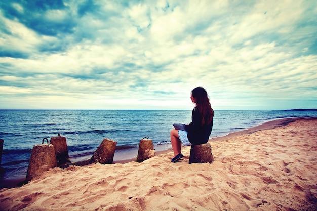 Traurige, einsame frau sitzt am strand.