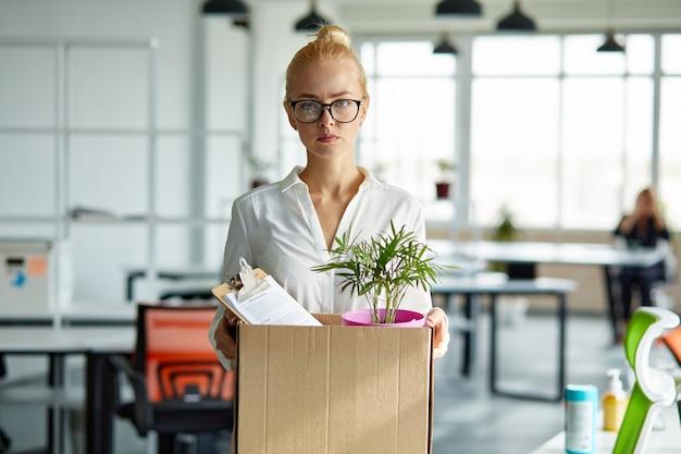 Traurige entlassene arbeiterin nimmt ihre büromaterialien aus dem büro