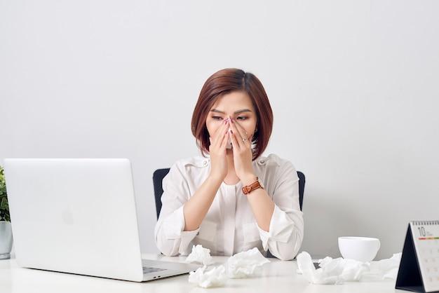 Traurige erschöpfte frau mit gewebe, das an kälte leidet, während mit laptop am tisch arbeiten