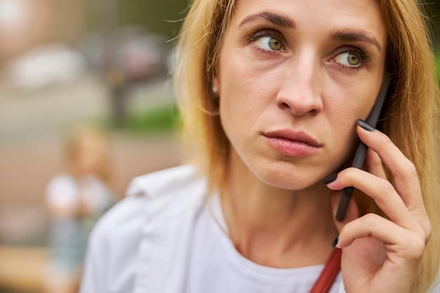 Traurige erwachsene frau, die im freien mit dem handy telefoniert