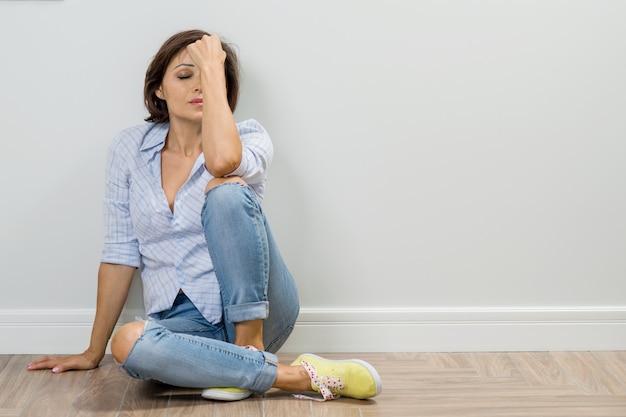 Traurige erwachsene frau in der krise sitzt auf dem boden des hauses