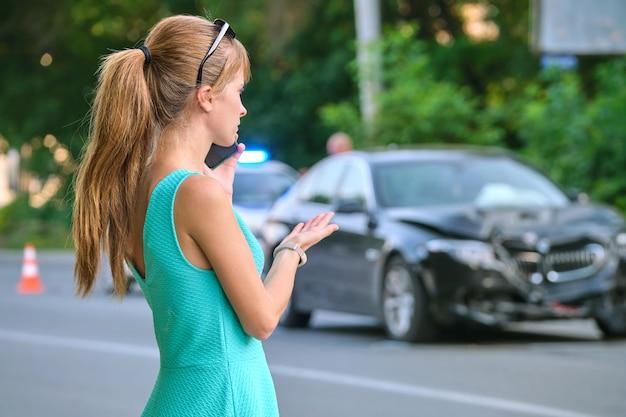 Traurige fahrerin, die auf der straßenseite am sellphone spricht und nach einem autounfall einen notdienst fordert. verkehrssicherheits- und versicherungskonzept.