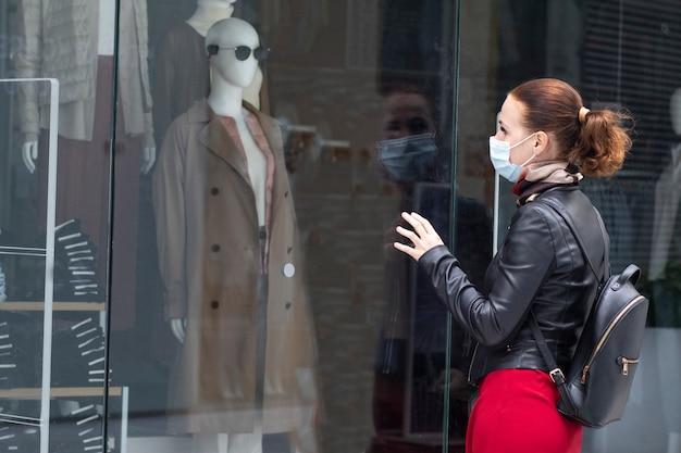 Traurige frau am eingang zu einem geschlossenen bekleidungsgeschäft in einem einkaufszentrum in einer maske auf ihrem gesicht. geschlossener laden, laden wegen quarantäne, coronavirus, covid-19