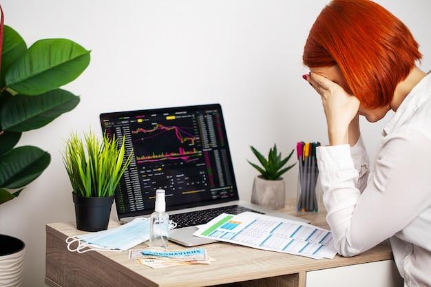 Traurige frau betrachtet fallende aktiencharts während einer epidemischen covid-19.