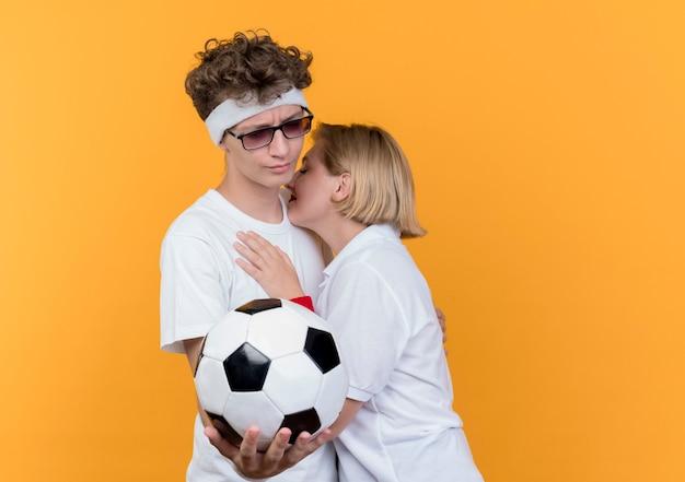 Traurige frau des jungen sportlichen paares, das mann umarmt, während er fußball hält, der über orange wand steht