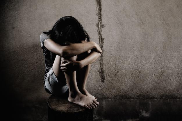 Traurige frau, die alleine in einem leeren raum sitzt